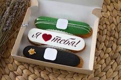 用不同的装填的三个开胃美丽的甜设计师小饼和在纸板箱的题字`我爱你` 免版税库存照片