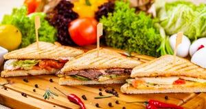 用不同的装填的三明治在木切板 库存图片