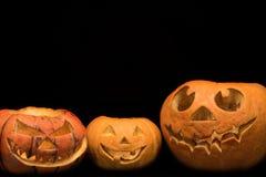 用不同的面孔的三个南瓜为假日在黑背景的万圣夜 免版税库存照片