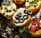 用不同的顶部的Crostini在黑暗的背景 可口的开胃菜 库存照片