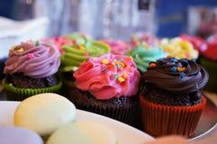 用不同的颜色和味道的可口杯形蛋糕 免版税库存照片