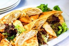 用不同的食物快餐和开胃菜用三明治,薄煎饼,在惊叹的新鲜的沙拉的美妙地装饰的承办的宴会桌 库存照片
