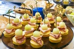 用不同的食物快餐和开胃菜的美丽的装饰的承办的宴会桌 点心板材用葡萄,乳酪 图库摄影