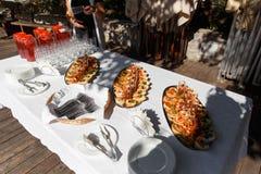 用不同的食物快餐和开胃菜的美妙地装饰的承办的宴会桌在公司圣诞节生日聚会事件 免版税库存图片