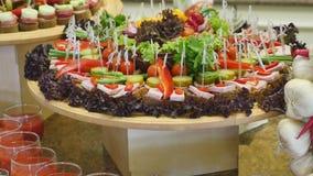 用不同的食物快餐和开胃菜的美妙地装饰的承办的宴会桌在公司圣诞节生日 库存照片