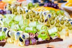 用不同的食物快餐和开胃菜的美妙地装饰的承办的宴会桌在公司圣诞节生日 免版税图库摄影