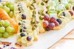 用不同的食物快餐和开胃菜的美妙地装饰的承办的宴会桌在公司圣诞节生日 免版税库存照片