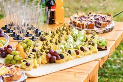 用不同的食物快餐和开胃菜的美妙地装饰的承办的宴会桌在公司圣诞节生日 免版税库存图片