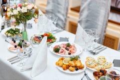 用不同的食物快餐和开胃菜的美妙地装饰的承办的宴会桌在公司生日聚会事件或weddin 库存图片