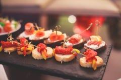 用不同的食物快餐和开胃菜的美妙地装饰的承办的宴会桌用三明治,鱼子酱,新鲜水果 免版税图库摄影