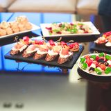 用不同的食物快餐和开胃菜的美妙地装饰的承办的宴会桌用三明治,鱼子酱,新鲜水果 免版税库存照片