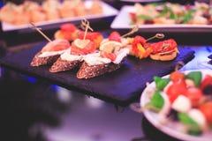 用不同的食物快餐和开胃菜的美妙地装饰的承办的宴会桌用三明治,鱼子酱,新鲜水果 库存照片