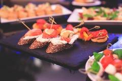 用不同的食物快餐和开胃菜的美妙地装饰的承办的宴会桌用三明治,鱼子酱,新鲜水果 库存图片