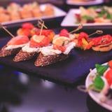 用不同的食物快餐和开胃菜的美妙地装饰的承办的宴会桌用三明治,鱼子酱,新鲜水果 免版税库存图片