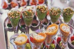 用不同的食物快餐和开胃菜的美妙地装饰的承办的宴会桌在公司圣诞节生日聚会事件 免版税库存照片