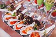 用不同的食物快餐和开胃菜的美妙地装饰的承办的宴会桌在公司圣诞节生日聚会事件 库存图片