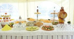 用不同的食物快餐和开胃菜的美妙地装饰的承办的宴会桌在公司圣诞节生日 影视素材