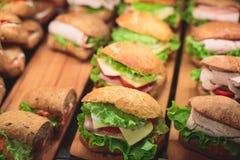 用不同的食物快餐和开胃菜的美妙地装饰的承办的宴会桌用三明治 库存图片