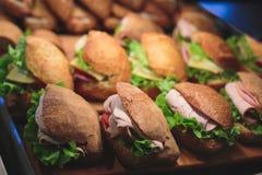 用不同的食物快餐和开胃菜的美妙地装饰的承办的宴会桌用三明治 库存照片