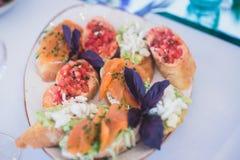 用不同的食物快餐和开胃菜的美妙地装饰的承办的宴会桌用三明治 免版税库存图片