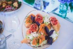 用不同的食物快餐和开胃菜的美妙地装饰的承办的宴会桌用三明治 免版税库存照片
