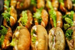 用不同的食物快餐和开胃菜的美妙地装饰的承办的宴会桌用三明治 图库摄影