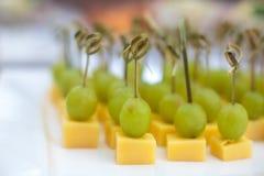用不同的食物快餐和开胃菜的美妙地装饰的承办的宴会桌 免版税图库摄影
