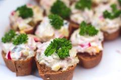 用不同的食物快餐和开胃菜的美妙地装饰的承办的宴会桌 免版税库存图片