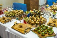 用不同的食物快餐的美丽的承办酒席为庆祝装饰的宴会桌和开胃菜集会 免版税库存图片