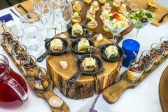 用不同的食物快餐的美丽的承办酒席为庆祝装饰的宴会桌和开胃菜集会 库存照片