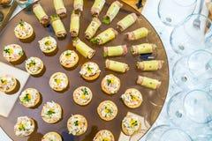 用不同的食物快餐,开胃菜的美妙地装饰的承办的宴会桌 免版税库存照片