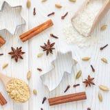 用不同的香料、面粉和曲奇饼切削刀的圣诞节背景在白色木桌,顶视图,方形的格式上 库存图片