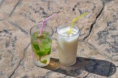 用不同的鸡尾酒的两块玻璃在s的石平板站立 免版税库存图片