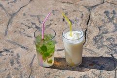 用不同的鸡尾酒的两块玻璃在s的石平板站立 库存照片