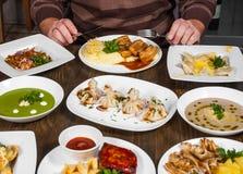 用不同的foodman手的盘有一把刀子和叉子的在桌上与许多另外食物 库存图片