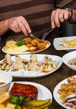 用不同的foodman手的盘有一把刀子和叉子的在桌上与许多另外食物 图库摄影