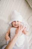 用与乐趣耳朵的白色竹毛巾盖的美丽的微笑的新出生的男婴 在白色编织,羊毛格子花呢披肩明亮的内部的谎言 免版税图库摄影