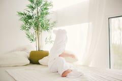 用与乐趣耳朵的白色竹毛巾盖的美丽的微笑的新出生的男婴 坐白色编织,羊毛格子花呢披肩明亮相互 免版税库存照片