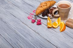 用与巧克力蛋糕的正确的新月形面包和在灰色木背景的一个桔子,其次洒与桃红色 图库摄影
