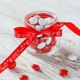 用与心脏的一把红色弓装饰的五颜六色的糖果瓶子在白色木背景 背景蓝色框概念概念性日礼品重点查出珠宝信函生活纤管红色仍然被塑造的华伦泰 免版税库存图片