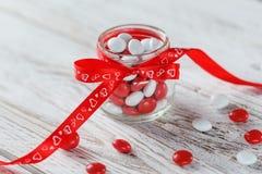 用与心脏的一把红色弓装饰的五颜六色的糖果瓶子在白色木背景 背景蓝色框概念概念性日礼品重点查出珠宝信函生活纤管红色仍然被塑造的华伦泰 库存图片