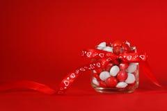 用与心脏的一把红色弓装饰的五颜六色的糖果瓶子在红色背景 背景蓝色框概念概念性日礼品重点查出珠宝信函生活纤管红色仍然被塑造的华伦泰 图库摄影