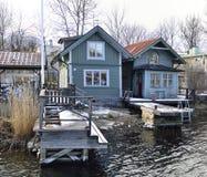 用与船坞的直接关系建造的两个绿色群岛房子小船的能手边 免版税库存照片