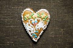 用两朵天鹅和花装饰的曲奇饼在粗麻布backgrou 库存图片