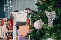 用中看不中用的物品和弓装饰的圣诞树在壁炉背景  库存照片