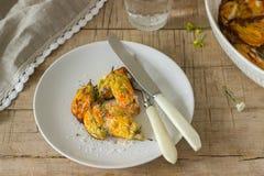 用乳清干酪和乳酪充塞烘烤了夏南瓜,并且南瓜花服务与一杯矿泉水 Rutik样式 免版税图库摄影