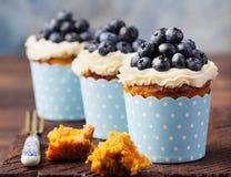 用乳脂干酪结霜和新鲜的蓝莓装饰的南瓜杯形蛋糕在木背景 免版税库存图片