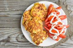 用乳酪涂的鸡胸脯,在白色板材的蕃茄,在老木桌上 免版税库存图片