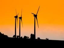 用于生态生产的电能的三台风轮机 日落剪影 免版税库存图片