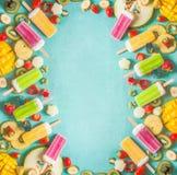 用五颜六色的冰淇凌冰棍儿做的框架用新鲜的切的果子和莓果成份在浅兰的背景,顶视图 库存照片